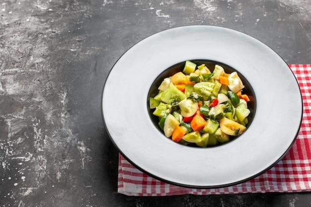 暗い背景の楕円形のプレートにグリーントマトサラダの底面図