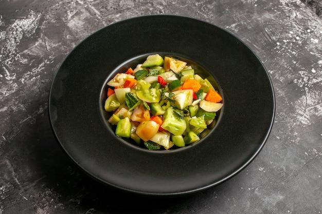 Вид снизу салат из зеленых помидоров на овальной тарелке на темном фоне