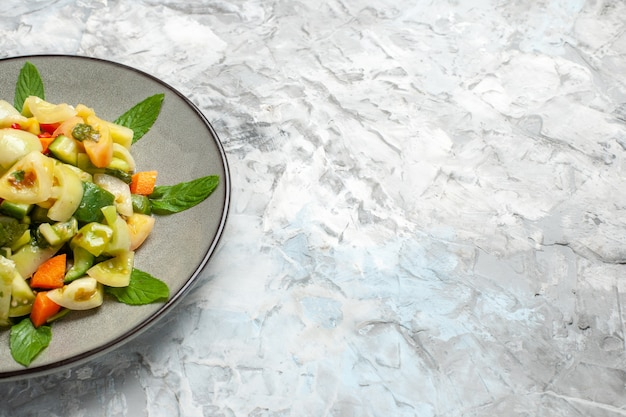 暗い上の楕円形のプレート上の底面図グリーントマトサラダ