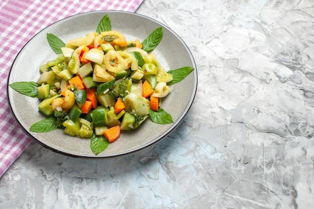 底面図楕円形のプレートにグリーントマトサラダピンクのテーブルクロスグレーに空きスペース