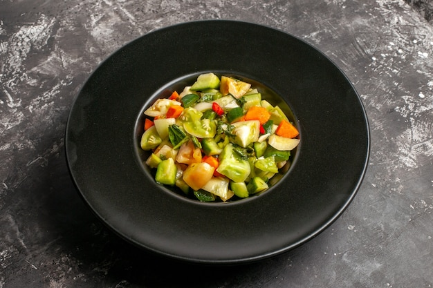 Bottom view green tomato salad on oval plate on dark background