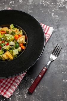 Insalata di pomodori verdi vista dal basso su piatto ovale una forchetta su sfondo scuro