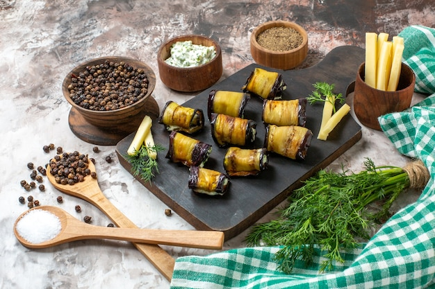Bottom view grilled eggplant rolls on wood chopping board spices in wooden spoons bunch of dill fries potates on nude background