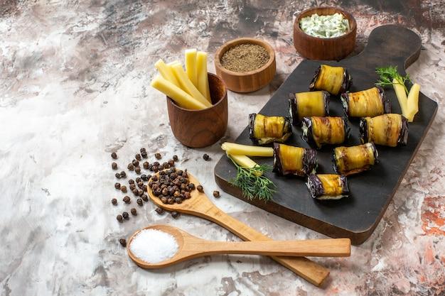 Vista dal basso involtini di melanzane grigliate su tagliere di legno spezie in cucchiai di legno su sfondo nudo