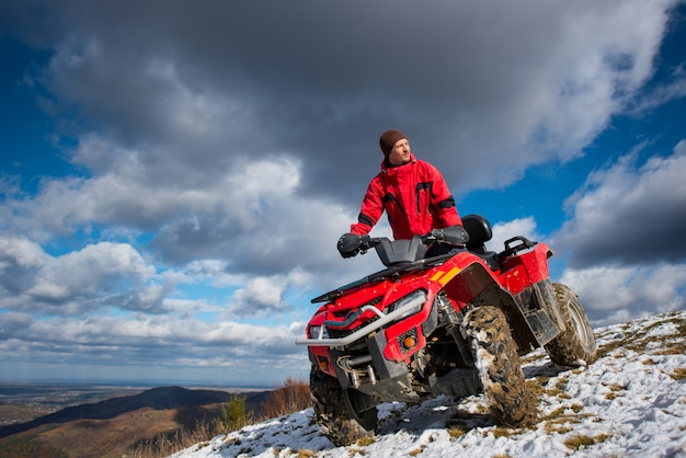 Bottom view of a guy on the sports atv quad bike at the snow-covered slope