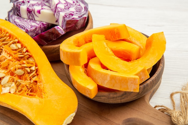 Bottom view half butternut squash red cabbage and squash slices in bowls on cutting board on white table