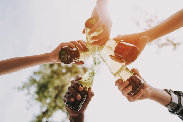 Bottom view hands of young people clink beer