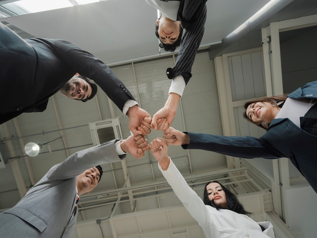 Bottom view of happy diverse business people team holding fists in circle, expressing unity and power in teamwork, multiethnic business people engaged in team building activity at briefing