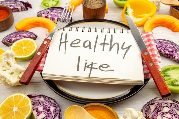 Vista dal basso vita sana scritta sulla forchetta e sul coltello del blocco note su un piatto rotondo taglia le verdure sul tavolo bianco