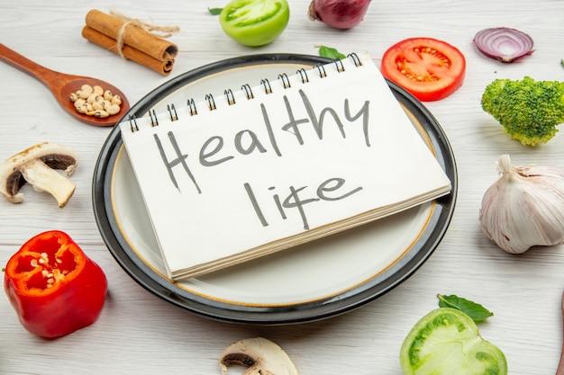 Vista dal basso vita sana scritta sul blocco note sul piatto cucchiaio di legno broccoli e altri animali sul tavolo