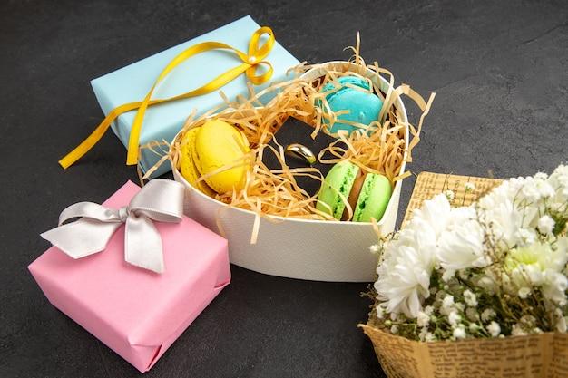 Вид снизу коробка в форме сердца с макаронами обручальное кольцо голубые розовые подарочные коробки букет цветов на темном фоне