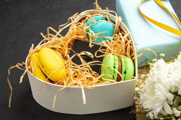 Вид снизу коробка в форме сердца с макаронами обручальное кольцо подарочный букет цветов на темном фоне