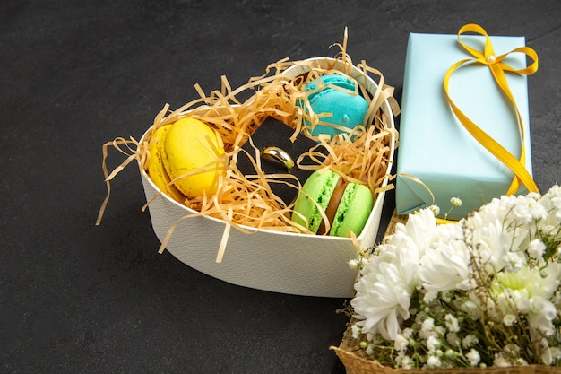 Коробка в форме сердца с соломенными макаронами и обручальное кольцо, подарочный букет цветов на темном фоне, вид снизу