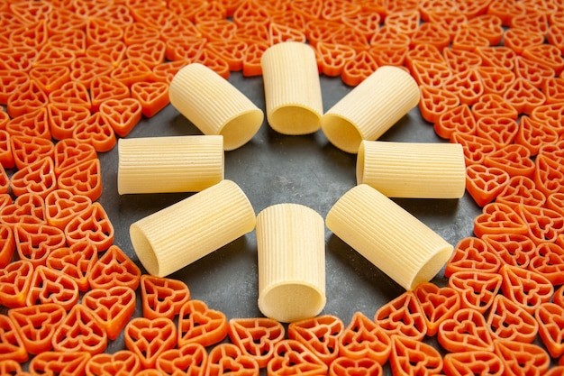 Bottom view heart shaped italian pasta and rigatoni on dark surface