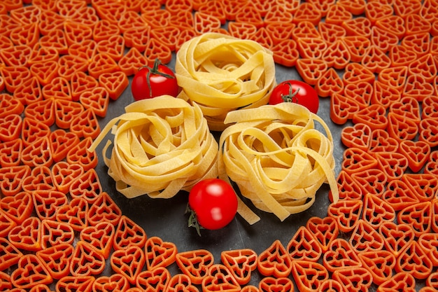 Bottom view heart shaped italian pasta tagliatelles and cherry tomatoes on empty place on dark surface