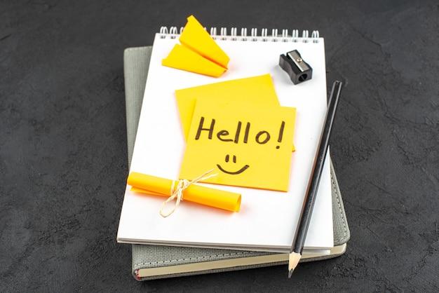 Bottom view hello written on yellow sticky note black pencil black pencil sharpener on notepad on dark background