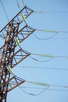 Bottom view on high voltage power lines against the blue cloudless sky