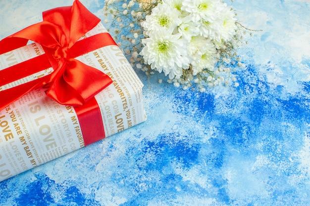 Вид снизу праздник подарки белые цветы на синем фоне свободное пространство