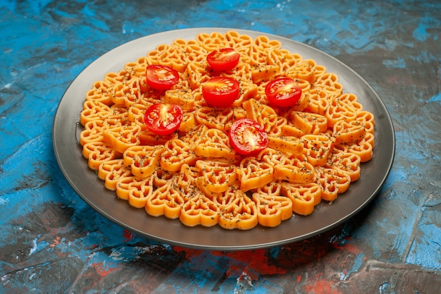 Bottom view italian pasta hearts cut cherry tomatoes on black oval plate on dark blue surface