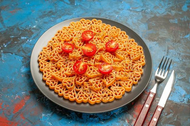 Vista dal basso i cuori di pasta italiana tagliano i pomodorini su forchetta e coltello in banda nera sul tavolo blu