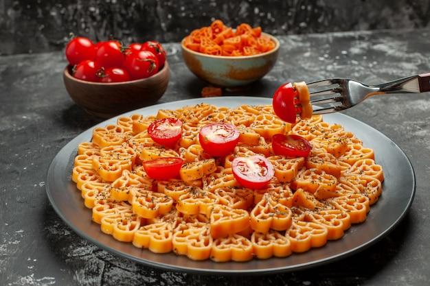 하단보기 이탈리아 파스타 마음은 타원형 접시 포크 체리 토마토와 회색 테이블에 그릇에 붉은 심장 파스타에 체리 토마토를 잘라