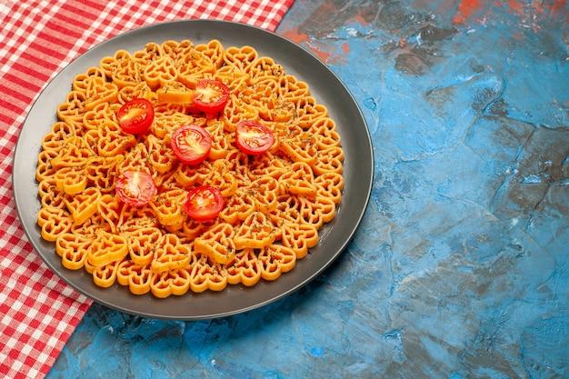 하단보기 이탈리아 파스타 하트 빨간색 흰색 체크 무늬 테이블에 타원형 접시에 체리 토마토를 잘라