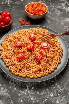 Bottom view italian pasta hearts cut cherry tomatoes on oval plate fork red heart pasta in bowl on grey table