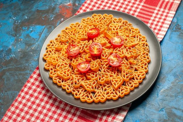 하단보기 이탈리아 파스타 하트 빨간색 흰색 체크 무늬 테이블에 타원형 접시에 토마토를 잘라