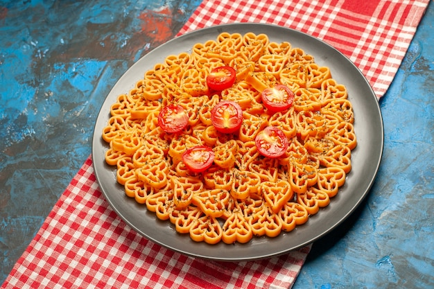 Bottom view italian pasta hearts cut tomatoes on oval plate on red white checkered table