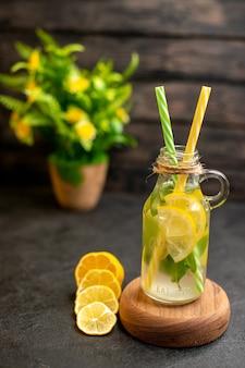 Vista dal basso pipette gialle e verdi di limonata su tavola di legno pianta in vaso di limoni tagliati su superficie di legno