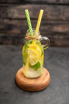 Vista dal basso pipette gialle e verdi di limonata su tavola di legno su superficie di legno