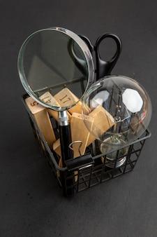 Vista dal basso lampadina lupa forbici rettangoli di legno in astuccio per penne su sfondo nero