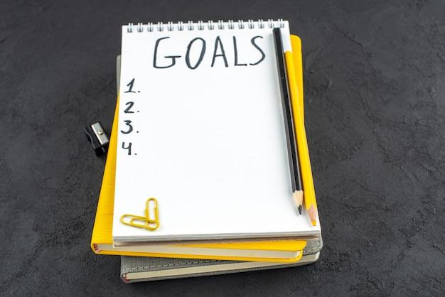 Вид снизу список целей, записанных на блокноте, точилка для карандашей, черные и желтые карандаши, клипсы с драгоценными камнями на темном фоне