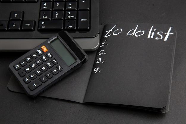 Vista dal basso per fare la lista scritta sulla tastiera della calcolatrice del blocco note sul tavolo nero