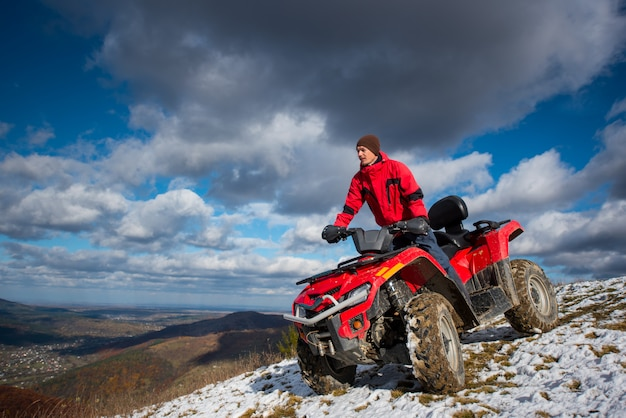 Bottom view of a man on the sports atv quadbike at the snow-covered hill against the blue cloudy sky on a sunny day in the highlands