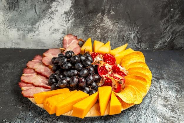Vista dal basso fette di carne formaggio uva e melograno su tagliere ovale su scuro on