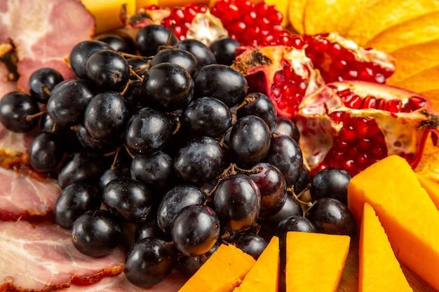 Vista dal basso fette di carne formaggio uva e melograno su tagliere ovale