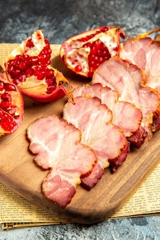 Bottom view meat slices cut pomegranate on chopping board on newspaper grey background