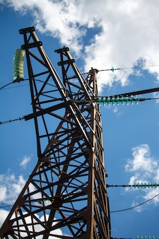 Bottom view of a metal pole of a power line with a multitude of electrical wires