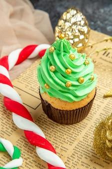 Vista dal basso mini cupcake natale caramelle ornamenti di natale su giornale beige tule scialle su oscurità