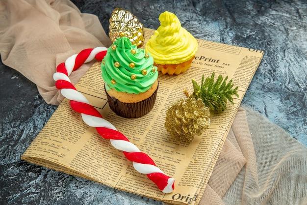 Vista dal basso mini cupcakes caramelle natalizie ornamenti natalizi su giornale scialle beige su oscurità