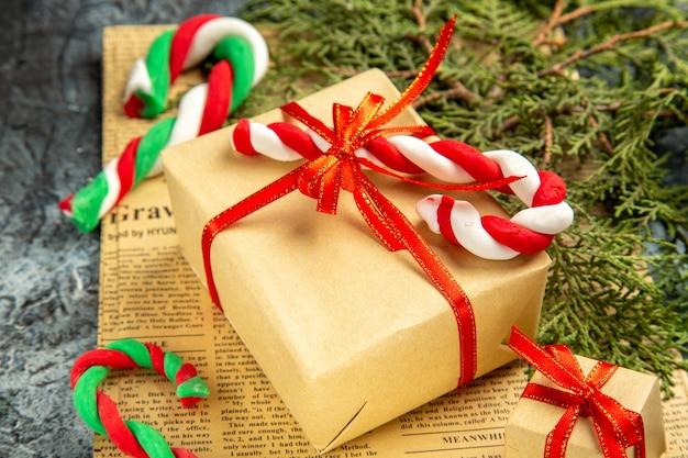 Вид снизу мини-подарок, перевязанный красной лентой, рождественские конфеты на газете на сером фоне