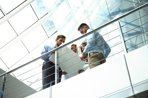 Вид снизу. современные люди в повседневной одежде проводят мозговой штурм, стоя в творческом офисе