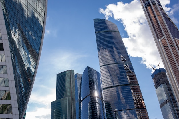 Bottom view of moscow-city skyscrapers with futuristic design with reflection of clouds