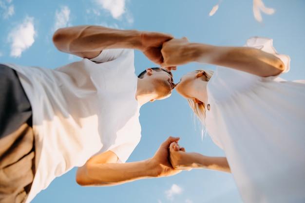 手をつないで、青い空の背景にキスをしているカップルの底面図。