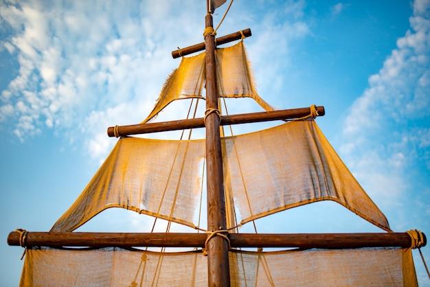 ベージュの帆が青い空を背景に揺れる船のマストの底面図