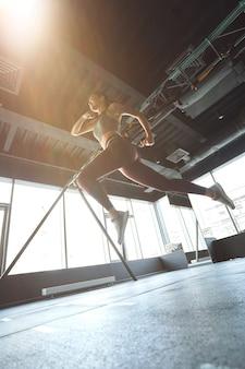 産業ジムで運動中にジャンプまたはランニングスポーツウェアの運動女性の底面図、垂直ショット。スポーツ、トレーニング、ウェルネス、健康的なライフスタイル