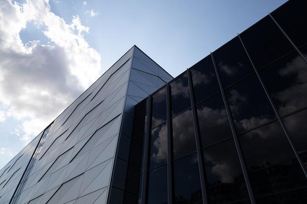 구름과 하늘을 반영하는 검은 유리로 만든 벽과 조각에 삼각형 패턴과 둥근 개구부가있는 건물의 밑면