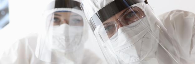 Вид снизу на врачей в противочумных защитных костюмах и экранах в больнице. концепция лечения covid-19