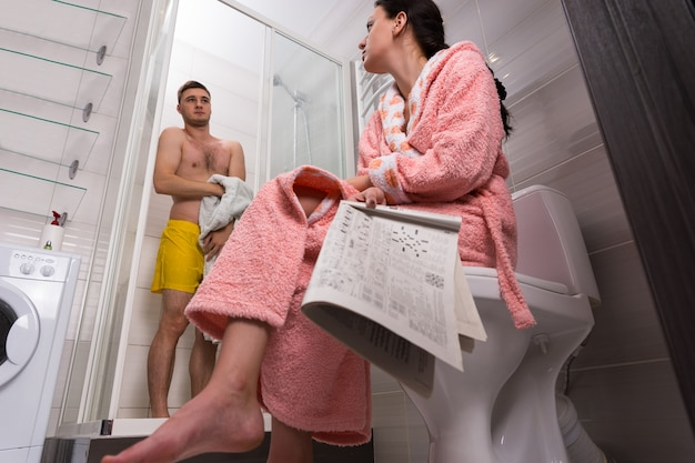 화장실에 신문이 있는 목욕 가운을 입은 여성의 밑면과 남자친구가 욕실에 투명한 유리문이 있는 샤워실에서 수건으로 닦는 동안 기다리는 동안